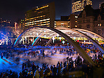 Toronto City Hall Nathan Phillips Square ice rink at night during Christmas season