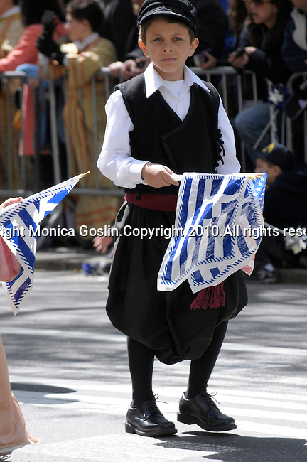 Greek Parade in New York City. A boy in traditional clothing and holding a Greek flag in the Greek Parade in New York City.