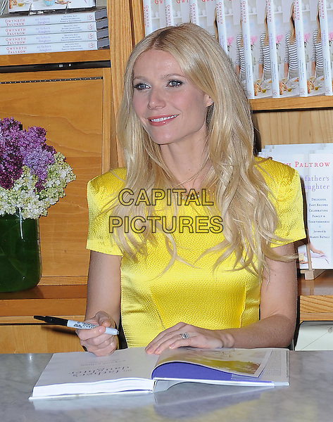 """GWYNETH PALTROW.Signs Copies Of """"My Father's Daughter: Delicious, Easy Recipes Celebrating Family & Togetherness"""" at Williams-Sonoma in Beverly Hills, California,.USA,  21st April 2011..half length book signing cook cookery yellow dress  sitting pen table .CAP/RKE/DVS.©DVS/RockinExposures/Capital Pictures."""
