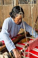 Yubei, Zhejiang, China.  Senior Woman Weaving at her Loom.