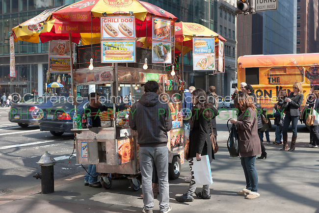 A street vendor cart selling hot dogs and other food works the corner of 5th Avenue and 42nd Street in New York City