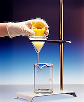 FILTERING A PRECIPITATE<br /> (1 of 3)<br /> Mixture Of Precipitated Lead And Water<br /> Mixture containing precipitated lead chromate and water is poured through filter paper in funnel.