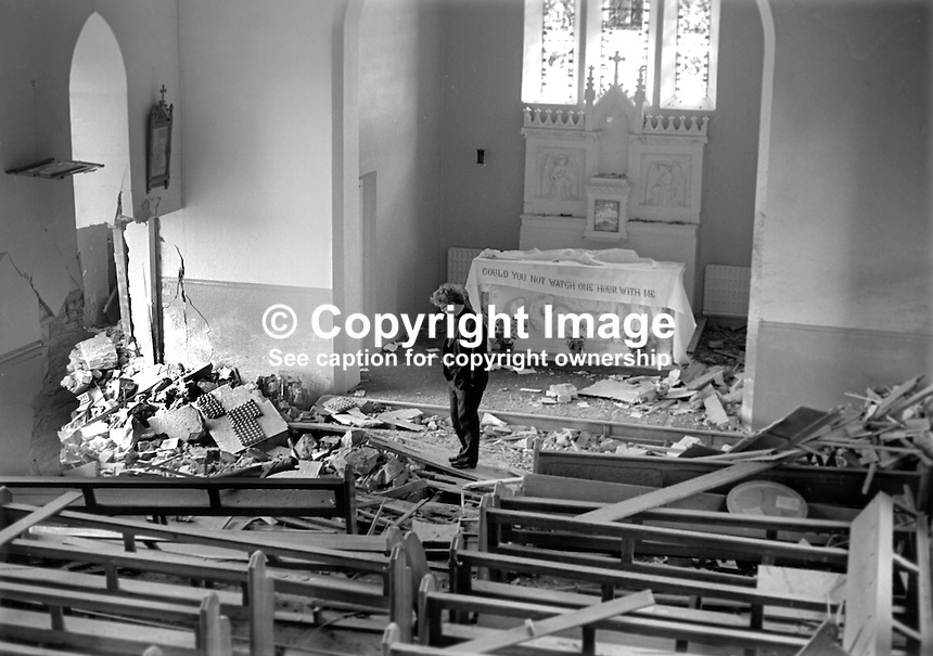 Rev James Poland, curate, St Mary's Roman Catholic Church, Kircubbin, Co Down, N Ireland, strikes a lonely figure standing in the rubble as he surveys the damage following a UDA/UFF bombing, 7th April 1974. 197406070311a<br />