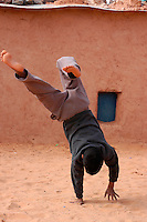 A boy plays on December 12, 2003, in the Saharawi refugee camps. Saharawi people have been living at the refugee camps of the Algerian desert named Hamada, or desert of the deserts, for more than 30 years now. Saharawi people have suffered the consecuences of European colonialism and the war against occupation by Moroccan forces. Polisario and Moroccan Army are in conflict since 1975 when Hassan II, Moroccan King in 1975, sent more than 250.000 civilians and soldiers to colonize the Western Sahara when Spain left the country. Since 1991 they are in a peace process without any outcome so far. (Ander Gillenea / Bostok Photo)