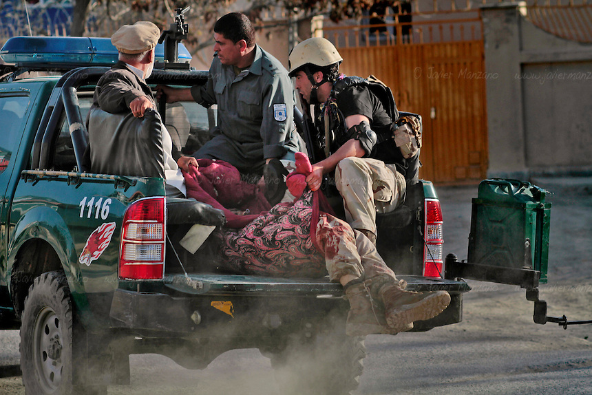 Afghan forces carry a wounded member of the Afghan Security Forces during one of several gun battles in Kabul today. Heavy weapons fire and rocket-propelled explosions could be heard across the Afghan capital city of Kabul on April 15th, 2012. ..Several targets were hit by alleged insurgents in and around the Shahre Naw and in Shash Darak areas of Kabul, where at least one rocket/mortar impacted the vicinity of the International Security Assistance Forces Headquarters. Heavy gunfire and explosions detonated around the Kabul Star Hotel and Azizi Bank (close to ISAF HQ). The gunfire began when an unconfirmed number of insurgents drove an SUV through the doors of a 5-story building (currently under construction) and used it as a base to launch attacks on ANSF and Norwegian Military Forces (who came to assist the Afghan Security forces). Casualties include one ANSF dead, four ANSF injured and an IMF wounded. ..It has further been confirmed that besides the attack at the Parliament complex earlier in the afternoon, ANSF interdicted a second tier attack in the vicinity of the 2nd Vice-President's residence and arrested two AOG equipped with BBIEDs and another infantry operative in the location..According to an ISAF press release, the attacks, which were concentrated in three clusters around the city, were  labeled  by the Taliban as the start of the so-called ?Spring Offensive? and were largely ineffective. .The attacks began just before 2:00 p.m. and consisted primarily of RPG and small arms fire.  Afghan Crisis Response Units along with Afghan police  and Army forces deployed to repel the attacks that resulted in light casualties while killing or capturing many of  the  suicide attackers in a matter of hours...National Directorate of Security announced that they had captured two suicide bombers alive before they were able to reach their intended targets. ..ISAF quick reaction forces were prepared to respond if required but were not needed.
