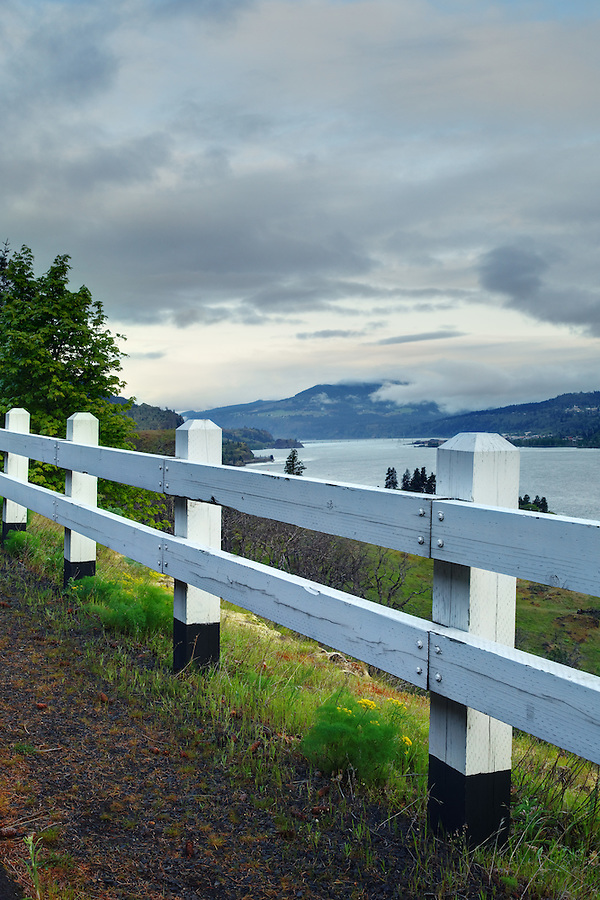 White wooden guard rail overlooking Columbia River along edge of Mosier Twin Tunnels Trail, Mosier, Oregon, USA