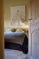 A glimpse into a simple bedroom decorated in a palette of brown and pale green colours