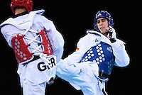 04 DEC 2011 - LONDON, GBR - Nicolas Garcia (ESP) (on right, in blue) battles with Alberto Celestrin (GER) (on left, in red) during their men's -80kg category contest at the London International Taekwondo Invitational and 2012 Olympic Games test event at the ExCel Exhibition Centre in London, Great Britain .(PHOTO (C) NIGEL FARROW)