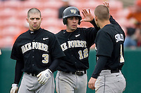 Carlos Lopez #12 of the Wake Forest Demon Deacons is congratulated by teammates Tyler Smith #3 and Austin Stadler #9 after scoring a run versus the Clemson Tigers at Doug Kingsmore stadium March 13, 2009 in Clemson, SC. (Photo by Brian Westerholt / Four Seam Images)