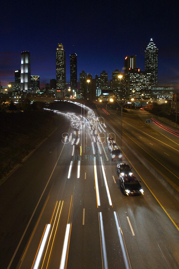 Cars move on Freedom Parkway under a skyline of downtown Atlanta, Georgia at sunset.
