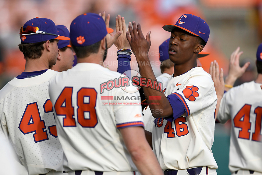 Starting pitcher Keyshawn Askew (46) of the Clemson Tigers is congratulated by Connor O'Rear (43) and Luke Sommerfield (48) after a scoreless inning in a game against the Charlotte 49ers on Monday, February 18, 2019, at Doug Kingsmore Stadium in Clemson, South Carolina. Clemson won, 7-6. (Tom Priddy/Four Seam Images)