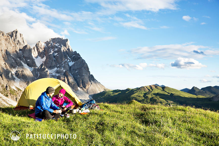 A couple outside their tent in the Italian Dolomites, cooking, relaxing and taking in the environment