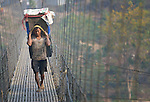 A man carries a load of merchandise on his back across a suspension bridge over the Trishuli River near the village of Buttar in the Gorkha District of Nepal.