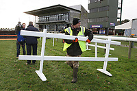 Groundsman Gary Eldridge uses a trestle to block off the fence by the finish line which was jumped by mistake at the last meeting - Horse Racing at Fakenham Racecourse, Norfolk