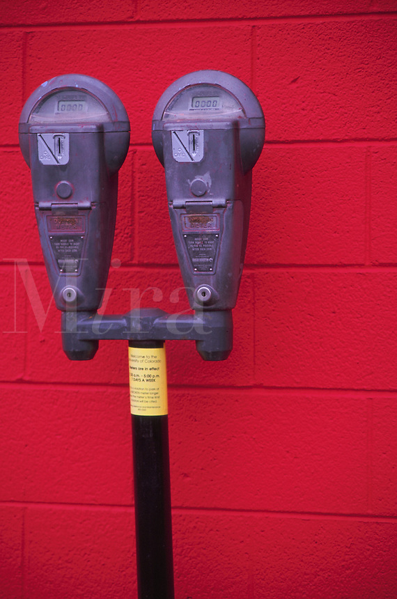 Graphic image of two parking meters in front of a bright, red brick wall. Each meter indicates 'Time Expired.'.