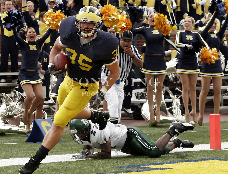 Michigan fullback Brian Thompson (35), defended by Eastern Michigan defensive back Jereme Perry (27),  scores a touchdown in the second quarter at Michigan Stadium in Ann Arbor, Mich., Saturday, Sept. 17, 2005. (AP Photo/Tony Ding)