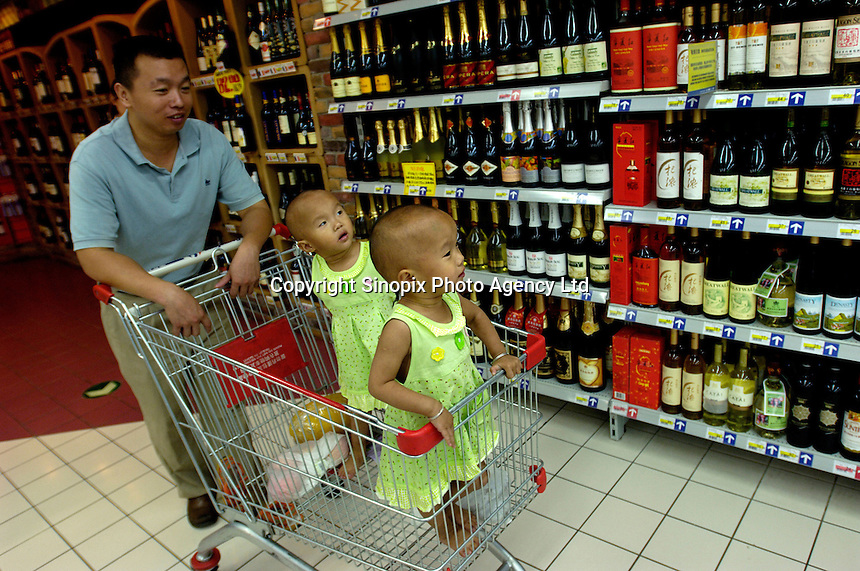 A man pushs a shopping cart with his two twins daughters at various Chinese wines in a Carrefour supermarket in Beijing, China. Major international chains like Carrefour and Walmart Stores have expanded aggressively in China. Local Chinese retailers have loudly protested this and lobbied heavily for protection from the new competition in price and service that these major retailers have set off..22 Jul 2006