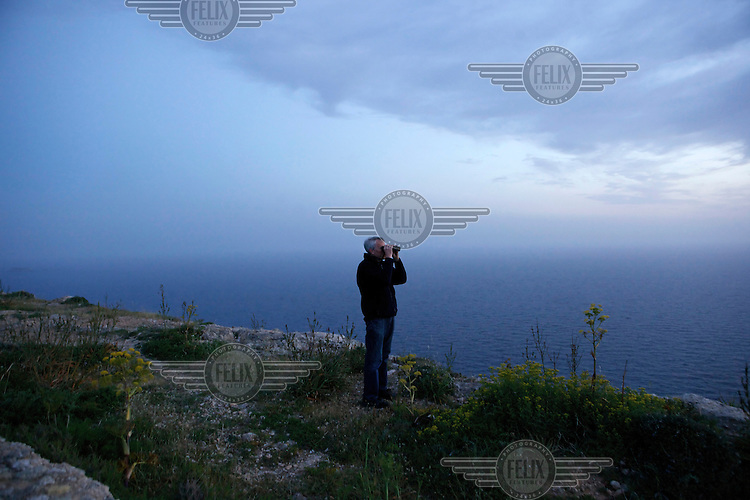A volunteer with Spring Watch Malta monitors the horizon for migrating birds.Under EU leglislation, hunting or trapping birds in spring is illegal but the government of Malta, which joined the EU in 2004, allows hunting of turtle dove and quail at this time of year. Some 170 species of bird pass over Malta during the spring and autumn migration periods. Hunters regularly shoot other species including birds of prey which are stuffed for private collection. Spring Watch Malta is a conservation camp run by BirdLife Malta, a non-profit which lobbies against bird hunting in the country. In 2012, fifty volunteers from across Europe converged on a tourist hotel in Bugibba in northern Malta and fanned out to track migrating birds and monitor any illegal spring hunting by the 11,000 permitted hunters.