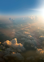 High aerial view of cumulus cloud formations catching the last sunlight