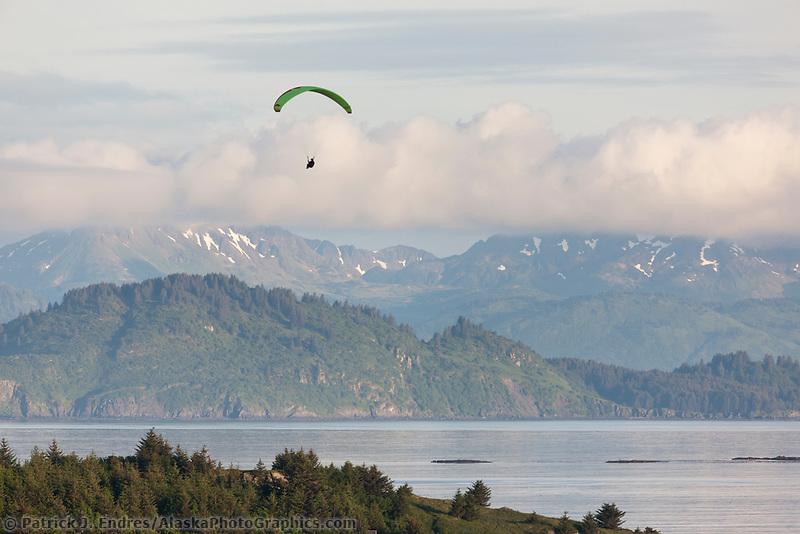 Paraglider drifts down to the island shore of Kodiak Island, Alaska.