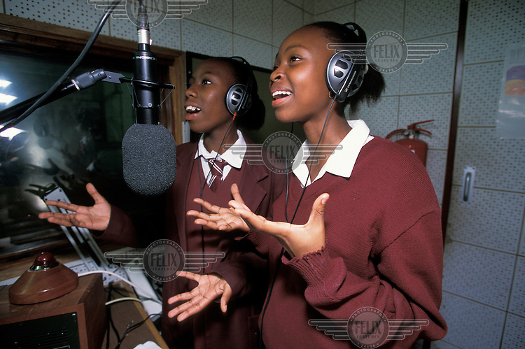 School girls participating in a youth radio programme at a local radio station.