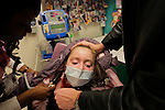 Sandra Massart, 10, has her temperature taken with help from her father William Massart, right, and nurse Benita Wyer, left, at Duke University Hospital in Durham, NC, USA, on Tuesday, Feb. 14, 2012.  Sandra Massart is being treated for MLD, a degenerative condition.  Photo by Ted Richardson
