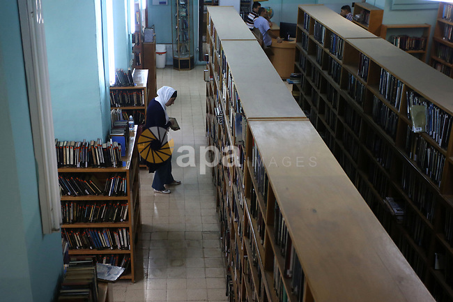 A Palestinian researcher selects a book at Nablus public library in the West Bank city of Nablus, on August 6, 2017. Nablus public library, the largest, and the oldest, in all of Palestine, opened in 1960, and library includes approximately 80,000 books, the majority of which are in Arabic. Besides the circulating collection, Nablus Library also houses several significant archival collections, including the so-called Prisoner's Section, an archive of materials made and used by Palestinian prisoners held in Israeli jails between 1975 and 1995, as well as the personal collection of Qadri Tuqan, a Nablusi educator and one of the founders of An-Najah College, now An-Najah National University.Other collections include Palestinian newspapers dating back to the 1920s. Photo by Ayman Ameen