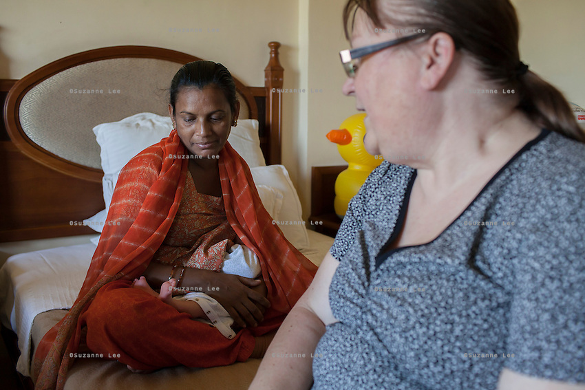 Barbara, from Canada, looks on as her surrogate, Idan, comes to breastfeed the baby in her hotel room near the Akanksha Clinic in Anand, Gujarat, India on 11th December 2012. Barbara, from Canada, had come to receive him at his birth from Idan, her surrogate, and is waiting for her husband to come and join her in Anand, while she continues to hire Idan to breastfeed her son so that he gets the best start in life. Idan's husband sends pumped breast milk to Barbara's hotel in the evenings when Idan cannot come personally. Photo by Suzanne Lee / Marie-Claire France