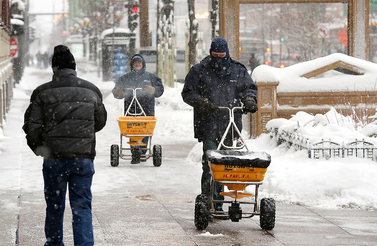 Mike Lesh (right, cq) and David Febo (left, cq) lay down a layer of salt to keep the sidewalks clear on the Loop campus of DePaul University in Chicago Thursday, Jan. 2, 2014. The New Year brought two days of lake effect snows to the downtown campus.  (Photo by Jamie Moncrief)
