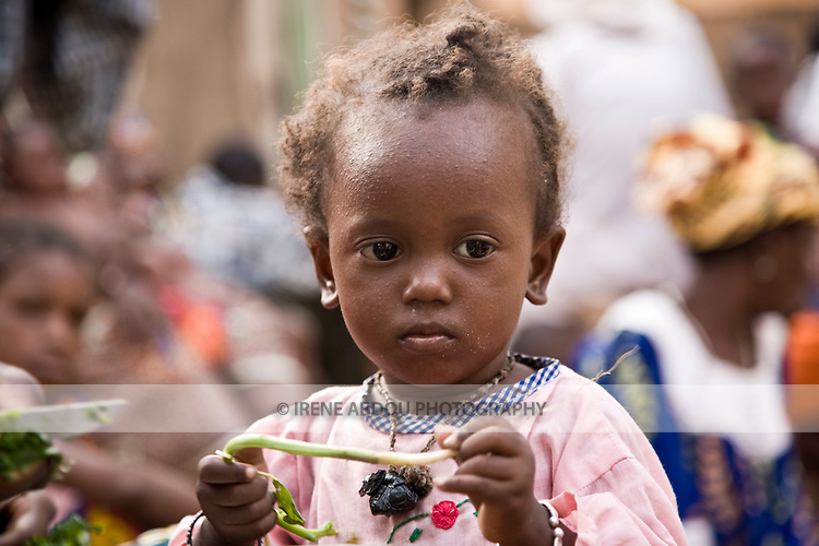 A young Fulani child in Ouagadougou, Burkina Faso, looks on as the women of the family prepare the evening's meal.