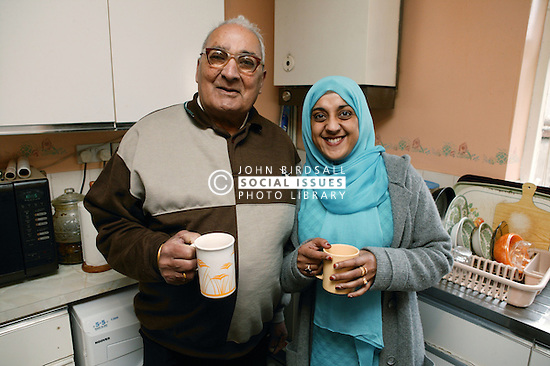 Asian carer with elderly Asian man in the kitchen chatting and drinking tea, ***NOT TO BE USED IN THE EAST MIDLANDS***