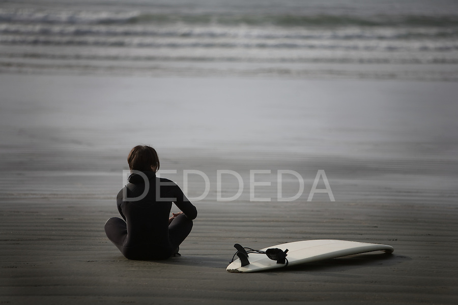 A male surfer in a wetsuit looks out over the beach before going surfing at Cox Bay near Tofino, British Columbia, Canada.