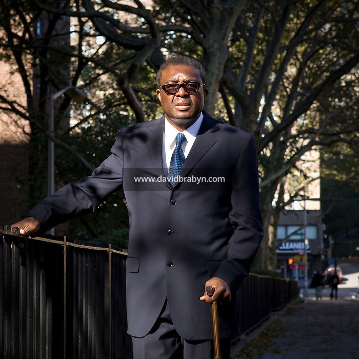 Robert Flowers, a retired county clerk, seen here on 131st street in Harlem, New York, NY, United States, poses for the photograph as he goes to church, 31 October 2008.