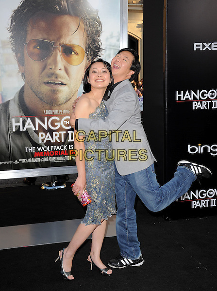 TRAN HO & KEN JEONG .at Warner Bros Pictures' L.A. Premiere of 'The Hangover Part 2' held at The Grauman's Chinese Theatre in Hollywood, California, USA, .May 19th 2011..full length grey gray jacket one shoulder dress    couple husband wife  gold lace blue     leg up funny hugging hug             .CAP/RKE/DVS.©DVS/RockinExposures/Capital Pictures.