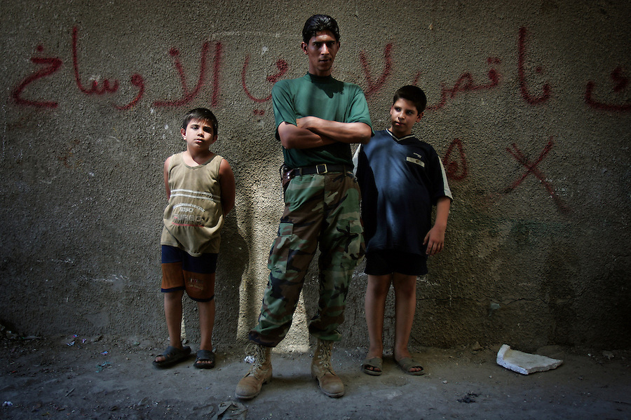 An Iraqi soldiers stands with two boys in an alleyway in the Sunni Baghdad district Adhamiyah on Friday September 1, 2006 .