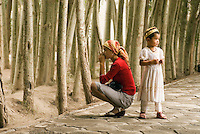 A Uyghur woman and child wait near the poplar trees that shelter the courtyard of the Id Kah Mosque.