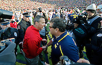Ohio State Buckeyes head coach Urban Meyer, left, and Michigan Wolverines head coach Brady Hoke shake hands after Ohio State Buckeyes beat Michigan Wolverines 42-41 during their college football game at Michigan Stadium in Ann Arbor, Michigan on November 30, 2013.  (Dispatch photo by Kyle Robertson)