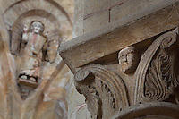 Carved capital with scrolls and a human face in the North transept, and behind, a carved and painted angel holding a speech scroll, in the lantern tower of the Abbatiale Sainte-Foy de Conques or Abbey-church of Saint-Foy, Conques, Aveyron, Midi-Pyrenees, France, a Romanesque abbey church begun 1050 under abbot Odolric to house the remains of St Foy, a 4th century female martyr. The church is on the pilgrimage route to Santiago da Compostela, and is listed as a historic monument and a UNESCO World Heritage Site. Picture by Manuel Cohen
