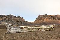 The remains of a water boat on the beach of Whalers Bay, Deception Island stands testament to the whaling history in the Antarctic region.  Water boats were used to bring freshwater from the land to the whaling ships anchored in the bay.  Neptune's Window (the gap between the cliffs) and the trail leading to it are seen in the background.