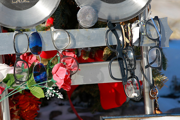 "1/19/12 3:42:10 PM -- Clear Lake, IA, U.S.A. -- THIS IS FOR A LIFE COVER:.Horn-rimmed glasses, flowers and a microphone hang from a memorial at the site of the 1959 plane crash that killed  Buddy Holly, Ritchie Valens and J.P. ""The Big Bopper"" Richardson a few miles outside of Clear Lake, Iowa..On Feb. 3, 1959, Buddy Holly, Ritchie Valens and the Big Bopper died when their plane crashed in a farm field north of Clear Lake, Iowa ? an event memorialized as ?the day the music died? in the 1971 song American Pie by Don McLean. The three 1950s stars played their last gigs at Clear Lake?s Surf Ballroom, which is intact today and holds an annual celebration of its moment in music history. The ballroom, largely the same as it was in its ?50s heyday, struggled as a for-profit business and has been operated as a non-profit since 2008. It hosts concerts, weddings, reunions and school tours. It has a small museum, but the big draw is the place itself. The maple dance floor and booths are original. One of the two original coat checks is still there and so is the phone that Holly used to call his wife before the fatal crash, the website boasts. The fun part is the annual gathering of fans from all over the world, which this year is Feb. 1-4 and is delicately called the ?winter dance party.? There are concerts each night, a bus outing to the crash site, which is marked by a giant pair of the glasses Holly wore, dance lessons, video and art contests and a gathering of the British Buddy Holly Society (whose members have been coming to Clear Lake for 23 years). Chuck Berry is a featured performer this year. It?s a charming and weird slice of Iowa life and rock ?n? roll history. -- ...Photo by Christopher Gannon for USA TODAY."