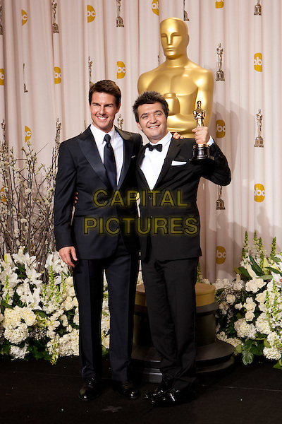 Tom Cruise and Oscar® Winner Thomas Langmann, winner for the category Best Motion Picture of the Year, pose backstage. The 84th Academy Awards® are presented live on the ABC Television network from the Hollywood and Highland Center, in Hollywood, CA, Sunday, February 26, 2012..*Editorial Use Only*.oscars award trophy winner full length black suit tuxedo.CAP/A.M.P.A.S./NFS.©A.M.P.A.S. Supplied by Capital Pictures.