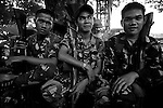 Members of the CATFU - Civilian Auxiliary Force Geographical Unit - a paramilitary group set up by the Philippine government to cheaply augment the armed forces - wait between patrols in a public park in Isabella City on the island of Basilan. Basilan is one of the sometime homes of the Islamist terrorist group Abu Sayyaf which is recent times has seen two of its top commanders killed by the army. The CATFU - like many poorly trained paramilitary groups - is often accused of perpetrating extrajudicial killings and human rights violations in the areas where they operate.