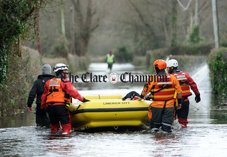 Emergency services personnel head off with a boat to rescue Springfield residents cut of due to flooding in their area. Photograph by John Kelly.