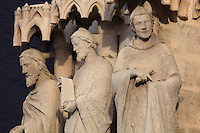 Statues of 3 of the 12 apostles, restored 1821-47 under Auguste Cheussey, by the sculptor Theophile Caudron, on the embrasures of the central portal, known as the Beau-Dieu portal, dedicated to the Last Judgment, on the Western facade of the Basilique Cathedrale Notre-Dame d'Amiens or Cathedral Basilica of Our Lady of Amiens, built 1220-70 in Gothic style, Amiens, Picardy, France. The ommission of several attributes when replacing the statues means the apostles are now difficult to recognise. Amiens Cathedral was listed as a UNESCO World Heritage Site in 1981. Picture by Manuel Cohen