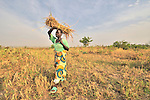 Peresi Nyoka brings home grass she has cut to use on the thatched roof of her hut in Yei, Southern Sudan. Ms. Nyoka is a United Methodist. NOTE: In July 2011, Southern Sudan became the independent country of South Sudan
