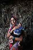 22 year old Seema Devi poses for a photograph with her 3 months old son, Krishna in the courtyard of their hut in Khurmaniya village in Raxaul district of Bihar. Seema Devi lost 5 of her children and her 6th child, Krishna was born in a government hospital. She is doing everything to make sure her son stays healthy.