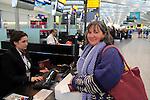 Woman checking-in at bag drop desk departure area terminal 5 Heathrow airport, London, England, UK