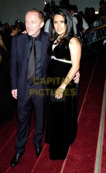 "FRANCOIS-HENRI PINAULT & SALMA HAYEK.2007 Metropolitan Museum of Art Costume Institute Gala celebrating ""Poiret: King of Fashion"" exibition at the Metropolitan Museum of Art, New York City, New York, USA..May 7th, 2007.full length black dress blue suit couple clutch purse bag .CAP/ADM/BL.©Bill Lyons/AdMedia/Capital Pictures *** Local Caption ***"