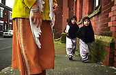 A mother waits while two young Muslim girls walk to the madrassa (Koran school) in Oldham, Northern England...Picture taken in 2001 by Justin Jin