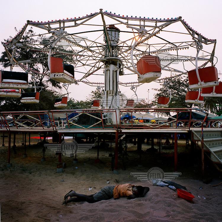 A boy sleeps on the sand near a funfair on the Ilha de Luanda..